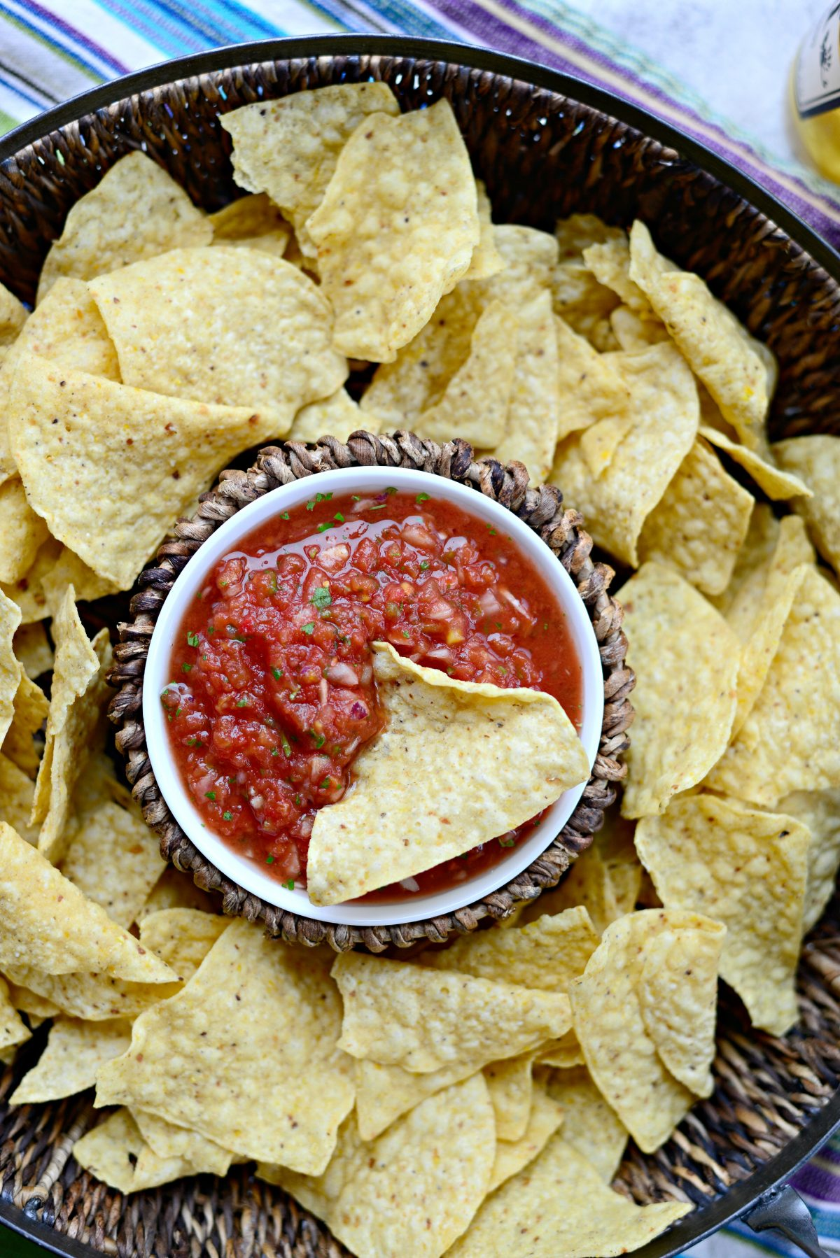 basket of tortilla chips with bowl of salsa in the middle