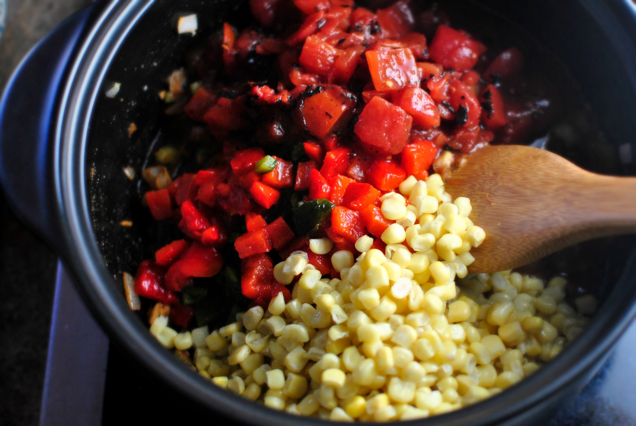Next add in the fire-roasted tomatoes, peppers, poblano and sweet corn ...