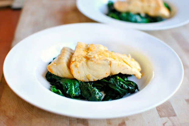 poached barramundi onto of spinach