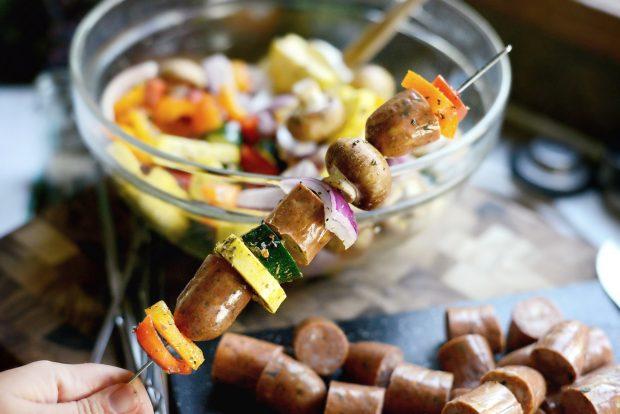 ingredients for chicken sausage vegetable kebabs skewered onto metal skewers