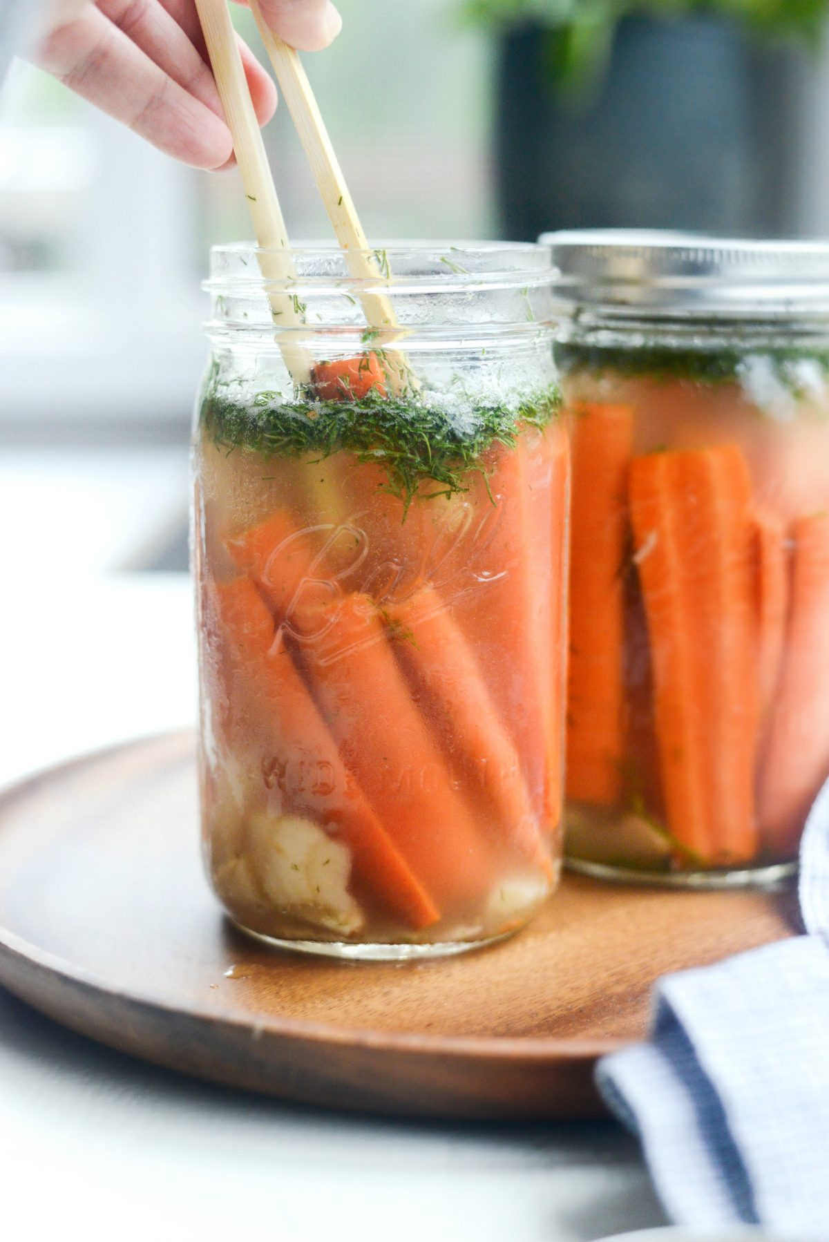 using bamboo tongs to remove Naturally Fermented Dilly Carrots from jar