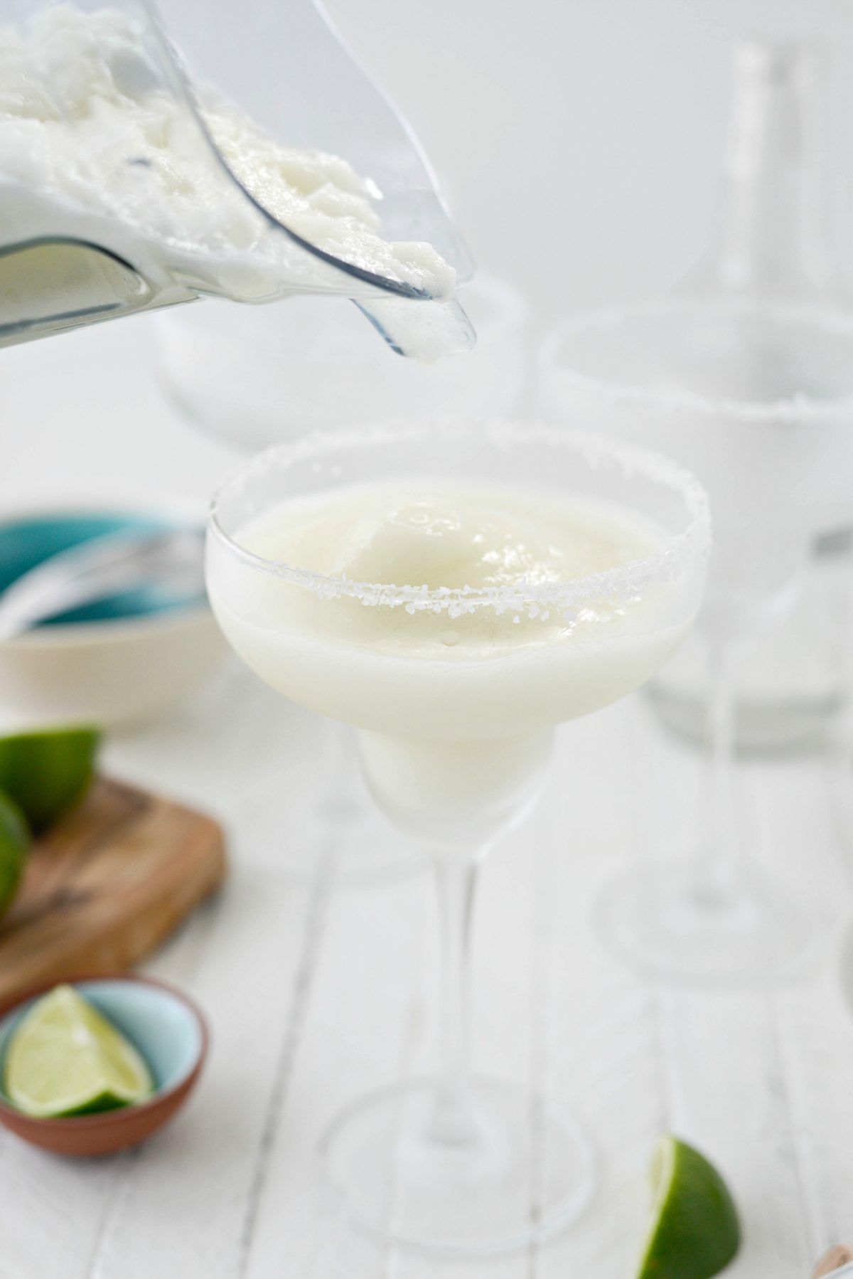 pouring Frozen Margarita Slush into frosted, salt rimmed glasses.