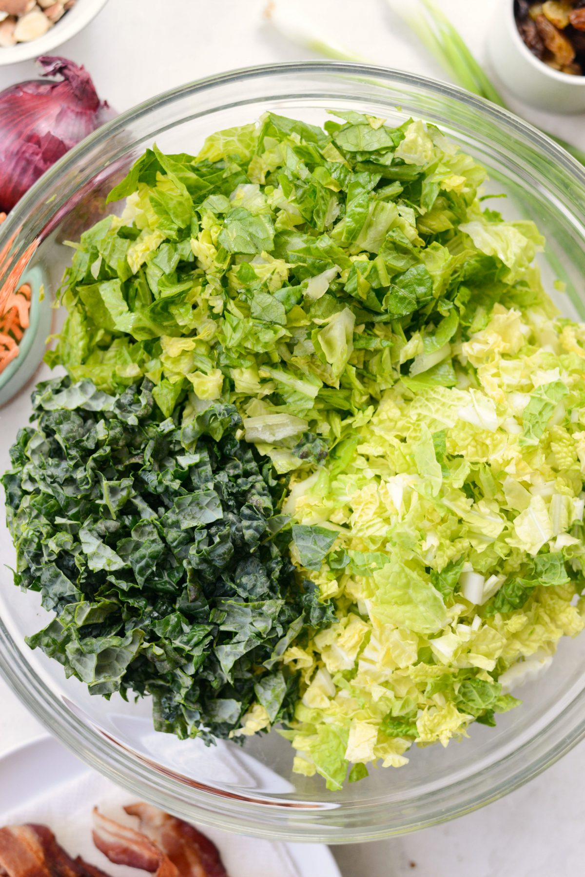 glass bowl of chopped lettuce and kale.