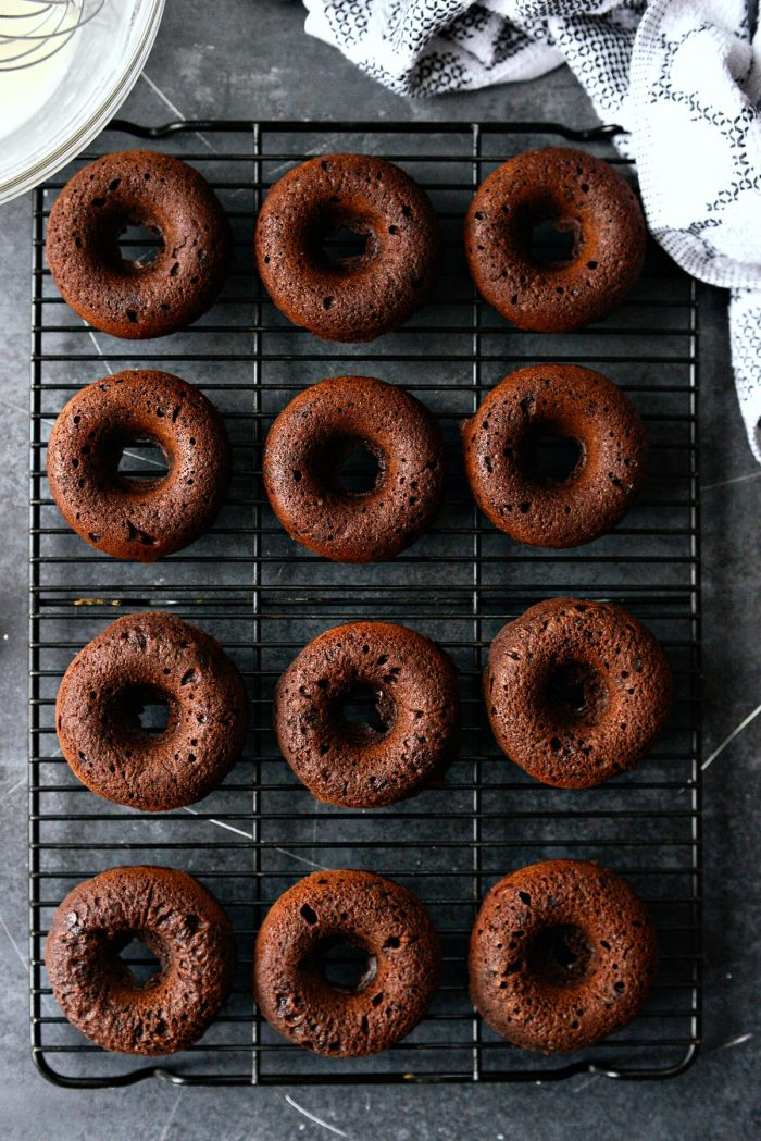 chocolate cake doughnuts inverted onto cooling rack.