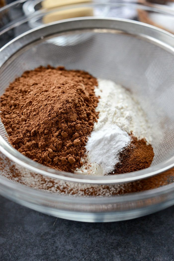 flour, cocoa powder, baking soda and instant espresso in a sieve set over a bowl.