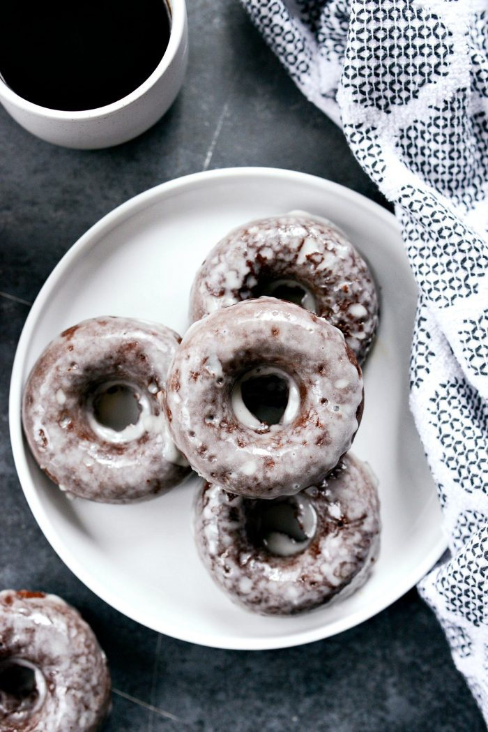 Glazed Chocolate Cake Doughnuts on a white plate with coffee