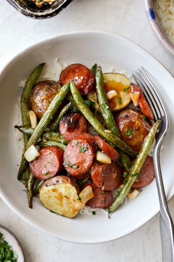 Honey Barbecue Sausage Sheet Pan Dinner - close up bowl of sausage, potatoes and green beans with fork