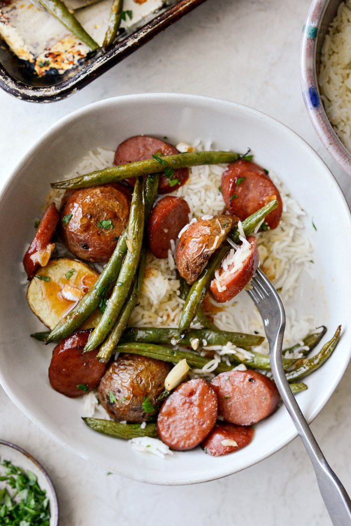 Honey Barbecue Sausage Sheet Pan Dinner - forkful of honey barbecue sausage, green bean and potato with white rice.