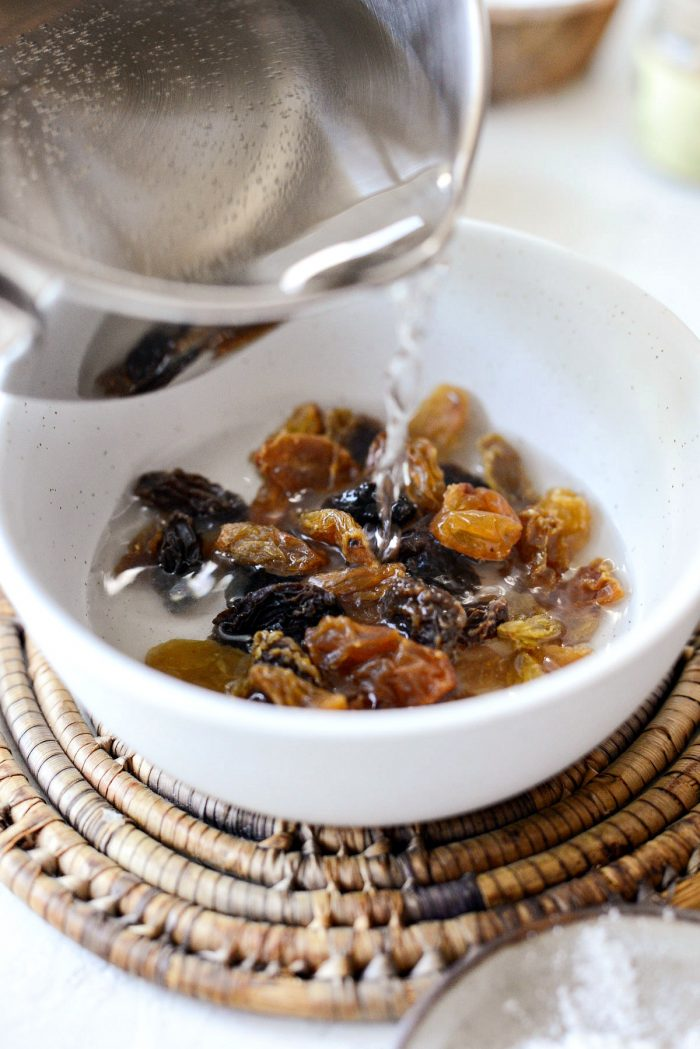 hot water pouring over raisins in white bowl.