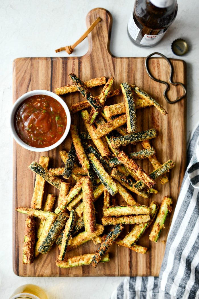 Air Fryer Zucchini Fries - top down shot of wood cutting board with zucchini fries, basil ketchup and a bottle of beer.