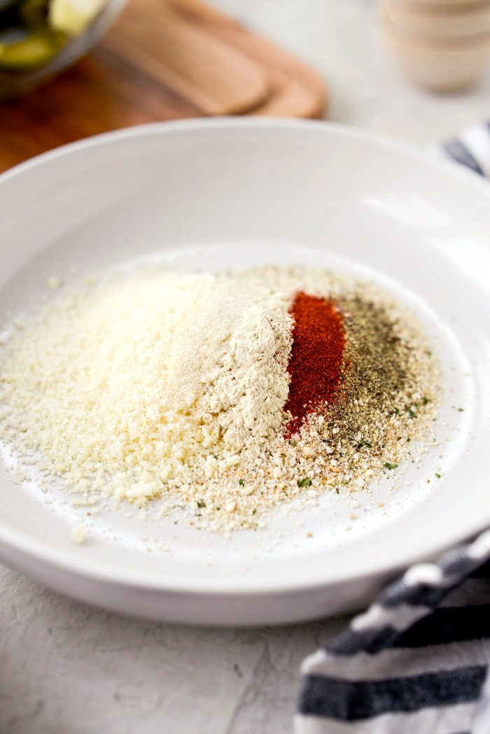 shallow bowl of italian breadcrumbs, parmesan cheese, paprika, kosher salt and black pepper, garlic and onion powder.