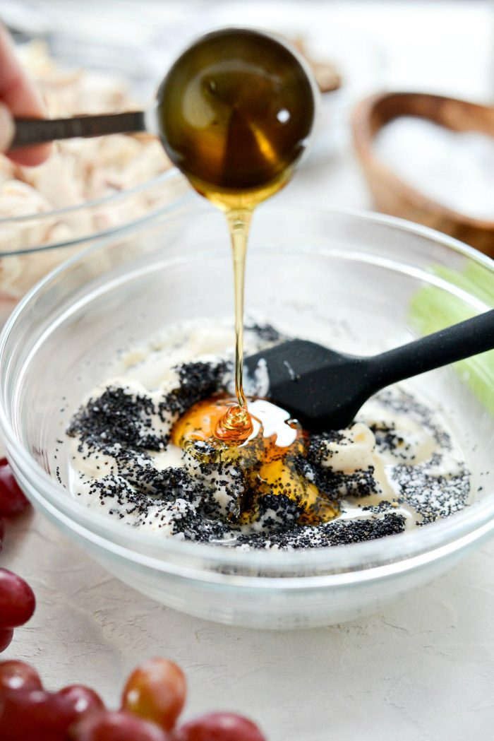 Pouring honey into bowl of remaining salad dressing ingredients.
