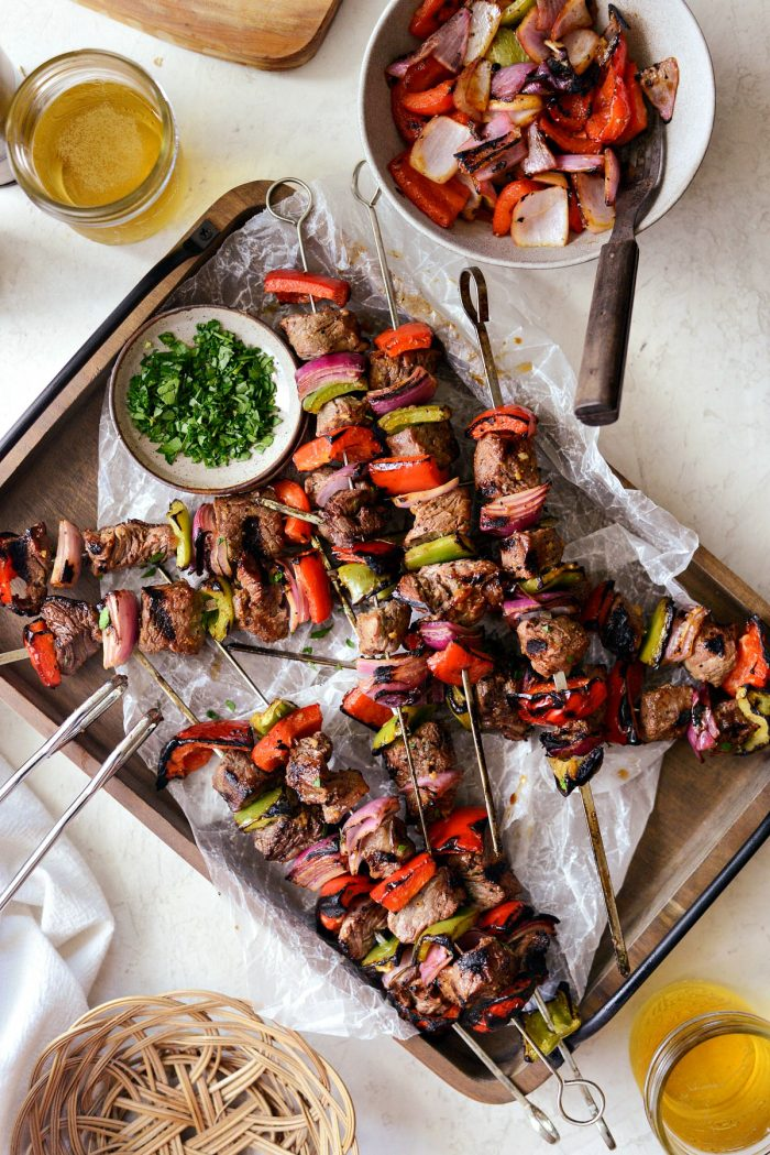grilled marinated steak kebabs on wooden tray with glasses of beer.