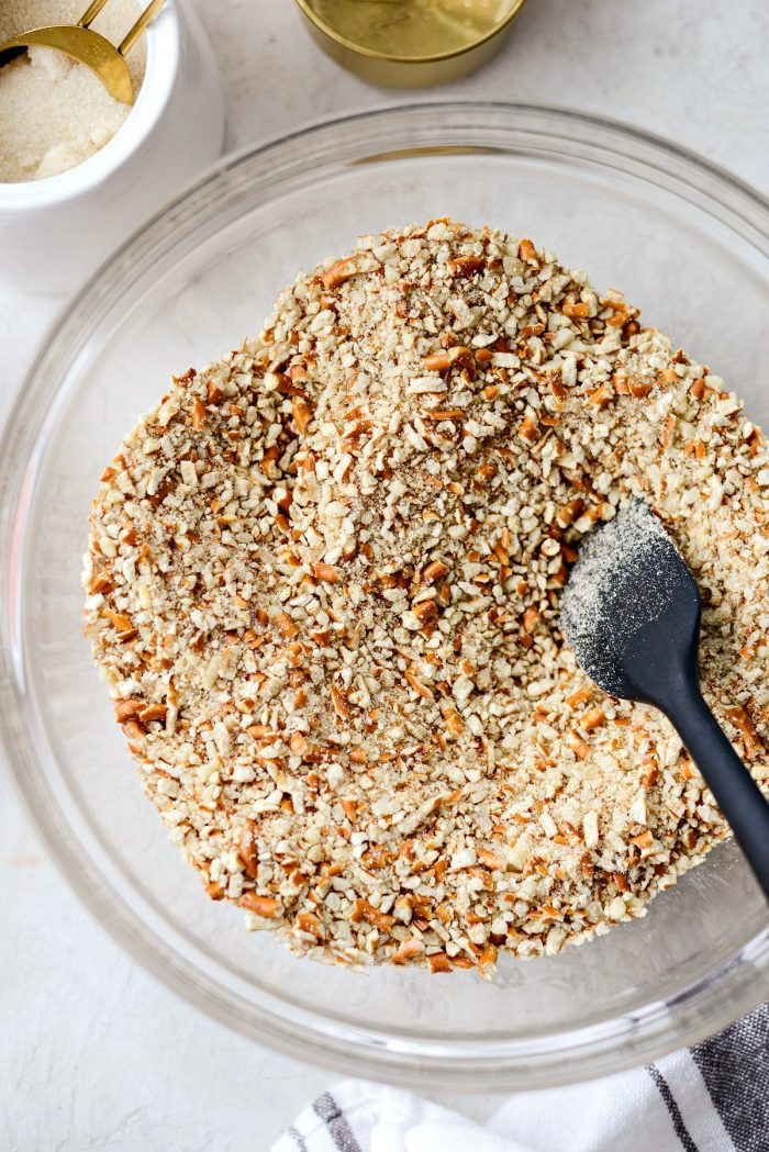 clear bowl of pretzel crumbs, ground almonds and sugar.