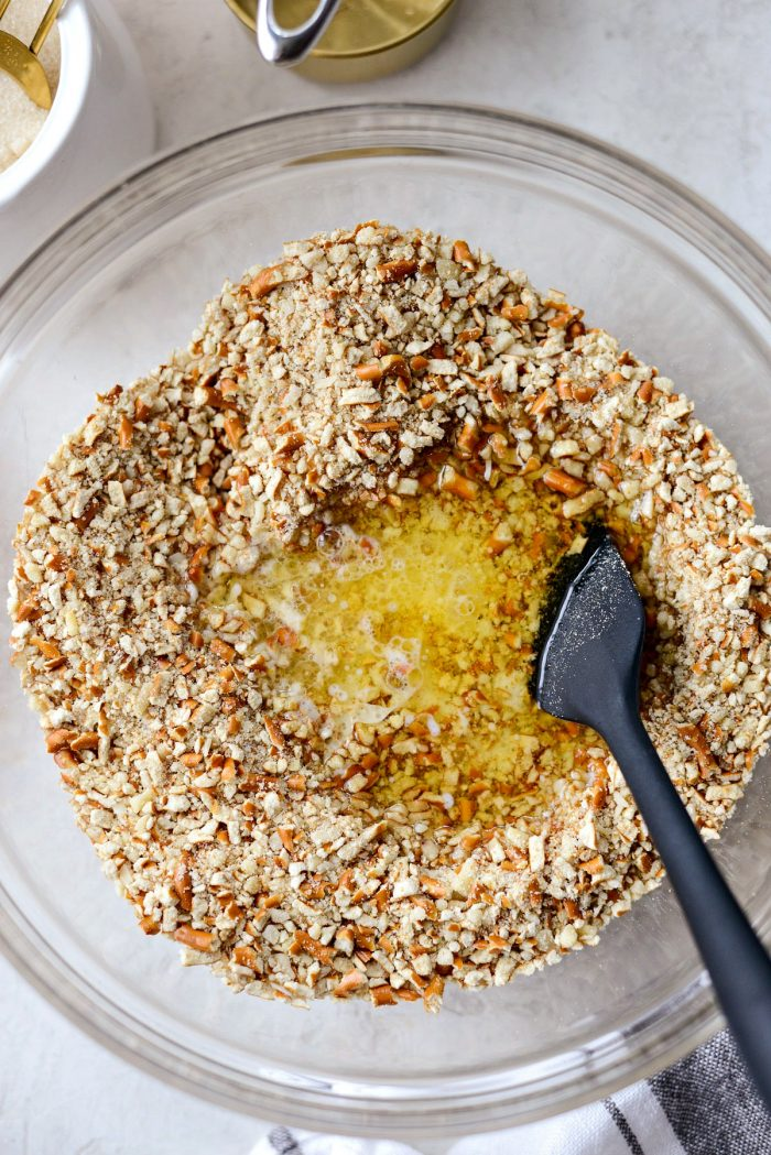 pouring butter into the pretzel and almond mixture.