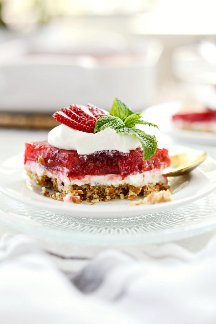 front view of strawberry pretzel dessert bars with bite missing to see visible layers.