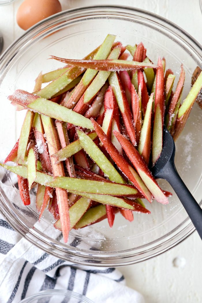 sliced rhubarb tossed with sugar in clear bowl.