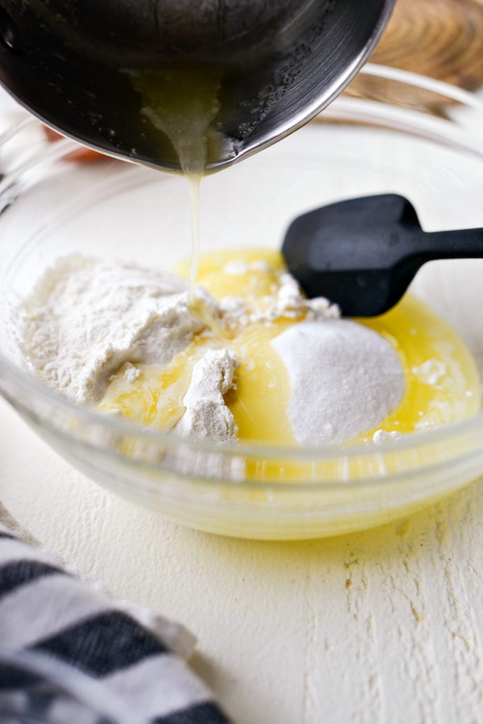 pouring butter into bowl with flour and sugar.