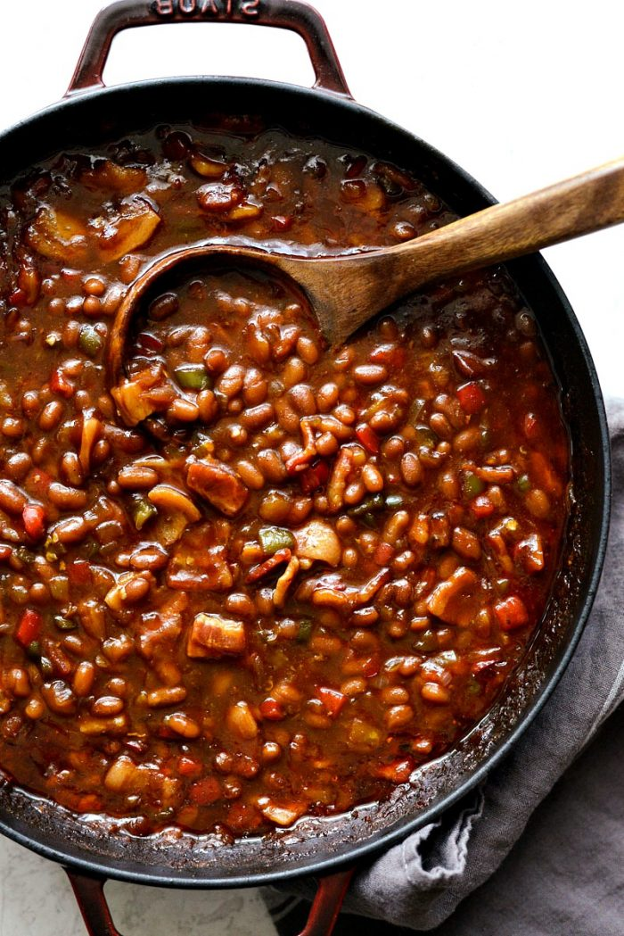 wooden spoon in red pot with one pot wicked baked beans