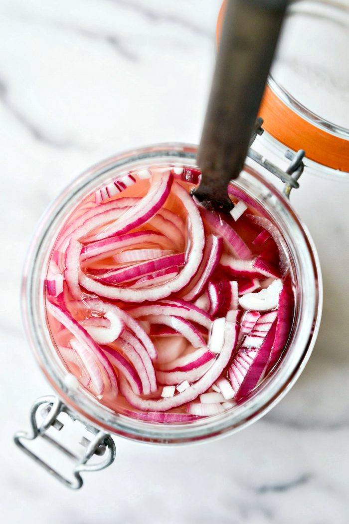 looking down into glass jar of quick pickled red onions.