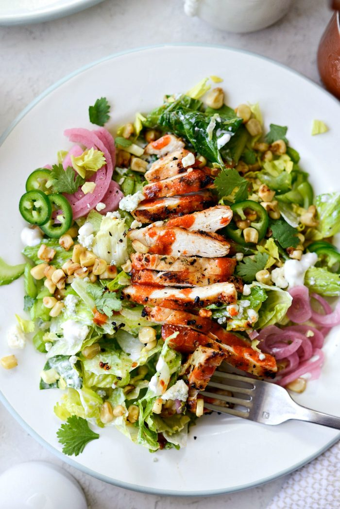 plate of buffalo grilled chicken salad with a forkful bite.
