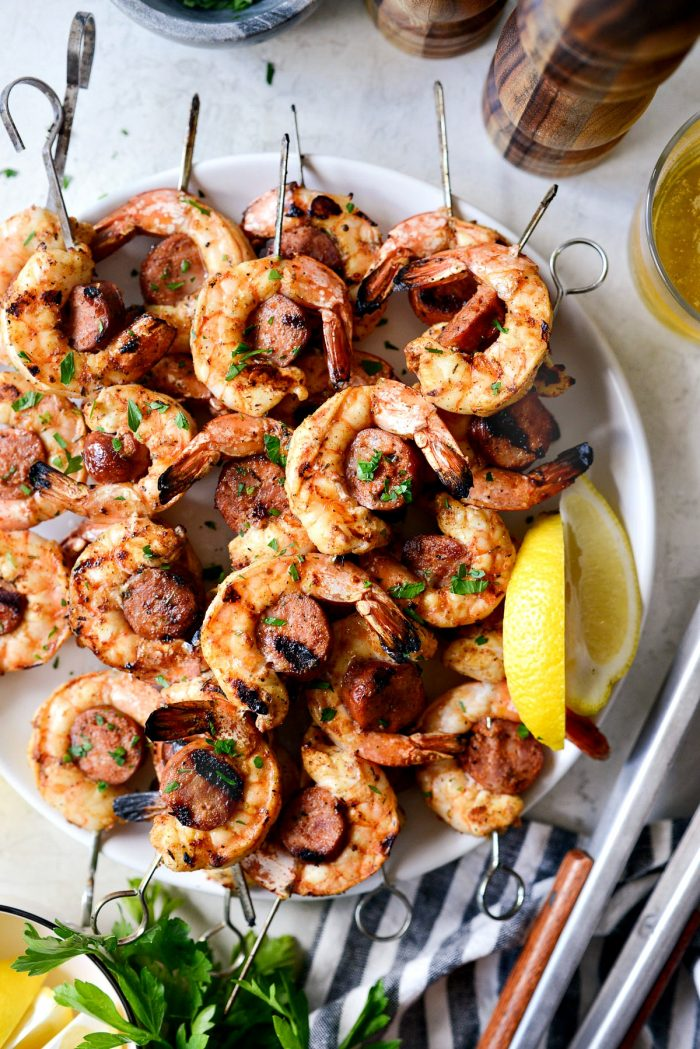 Grilled Cajun Shrimp and Andouille Skewers on white plate with lemon wedges.