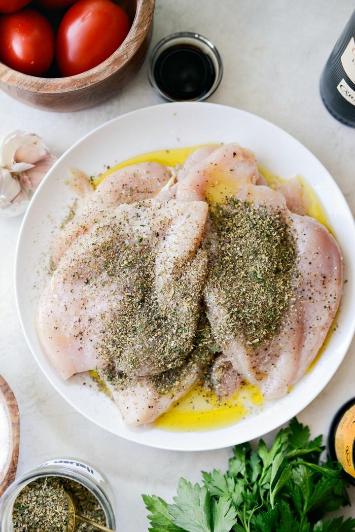 thinly pounded chicken on white plate with italian seasoning, lemon juice, olive oil, s & p