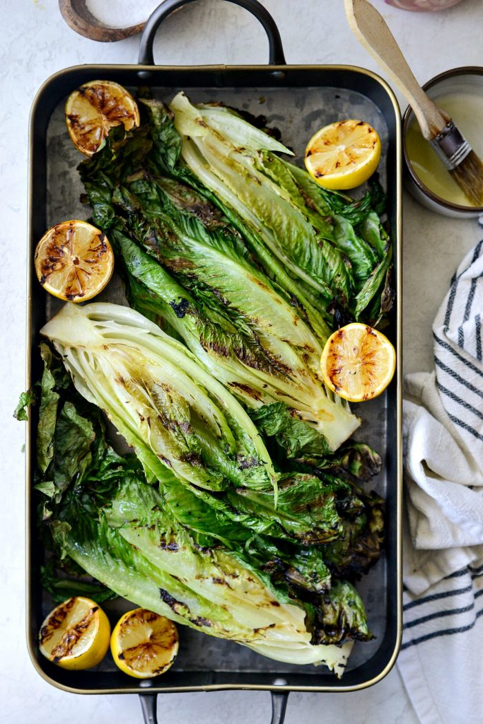 grilled romaine lettuce on a black metal serving tray