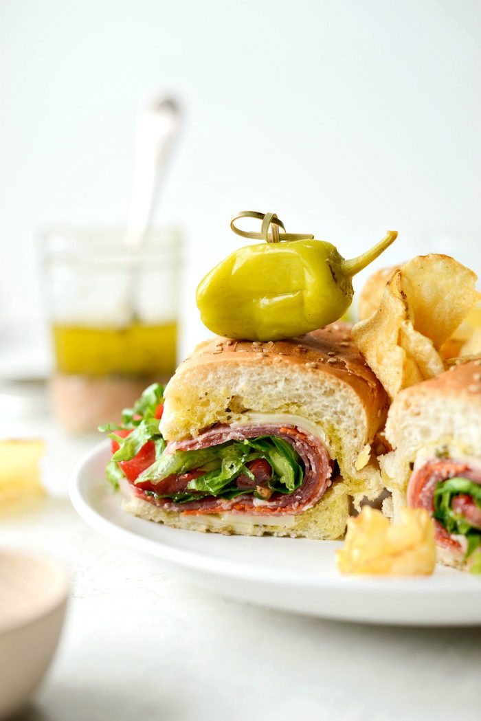 close up of italian sub sandwich with chips and peperoncini