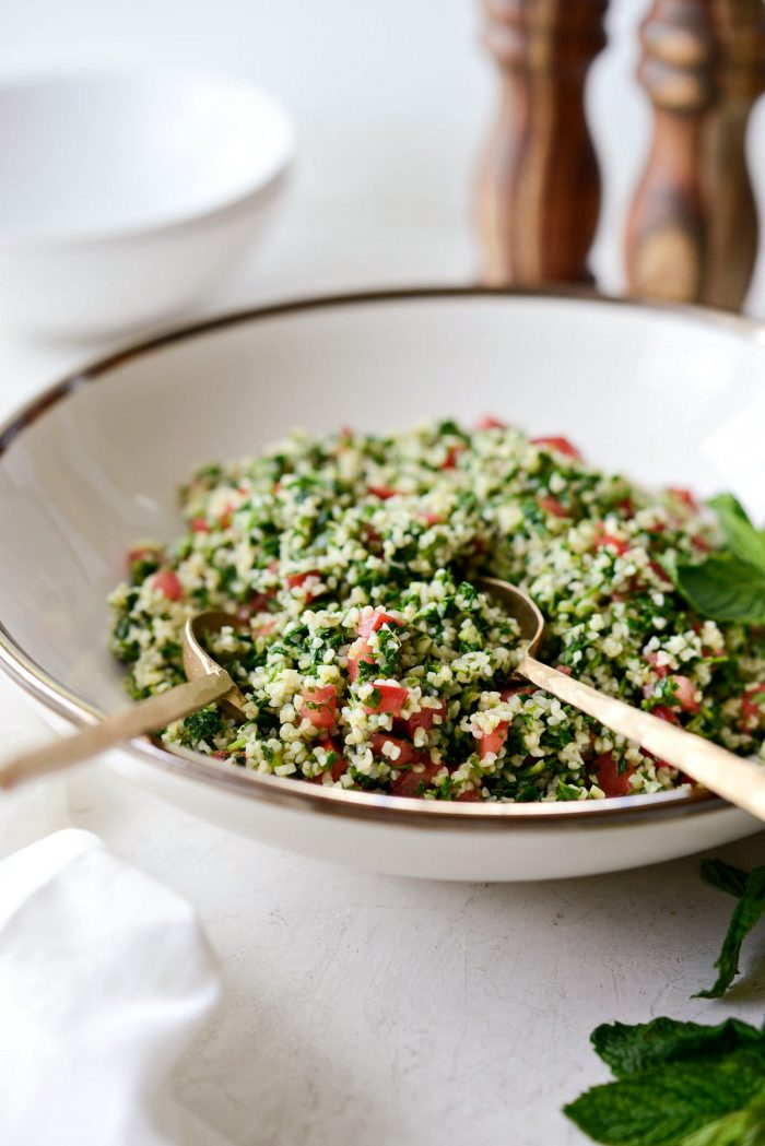 gold spoons in a bowl of homemade tabbouleh.