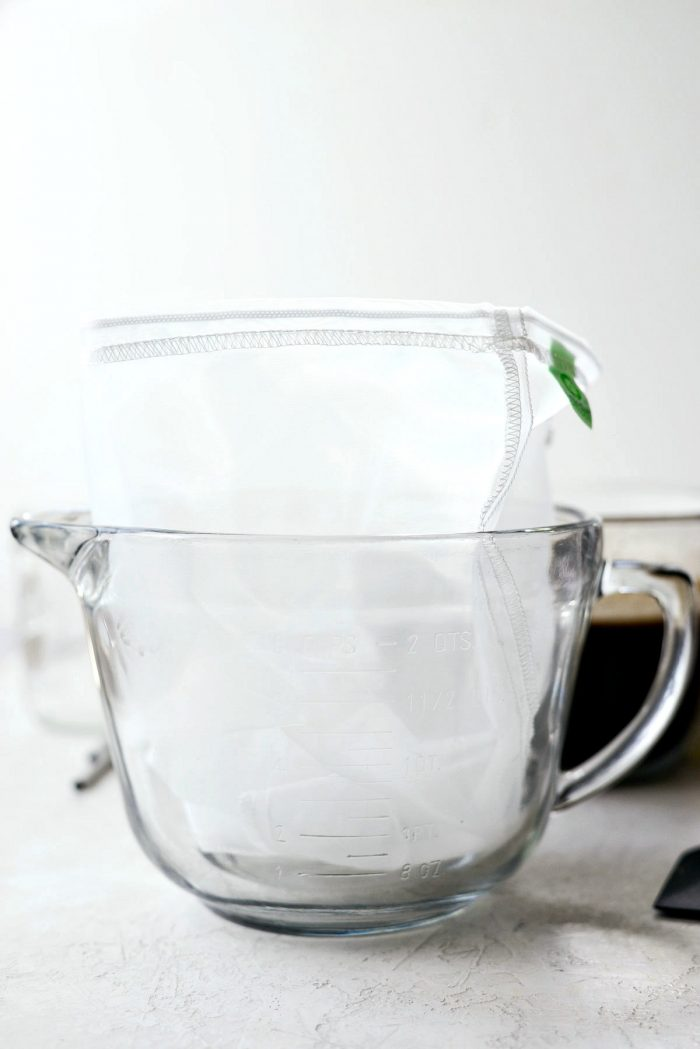 large glass measuring cup with nut milk bag