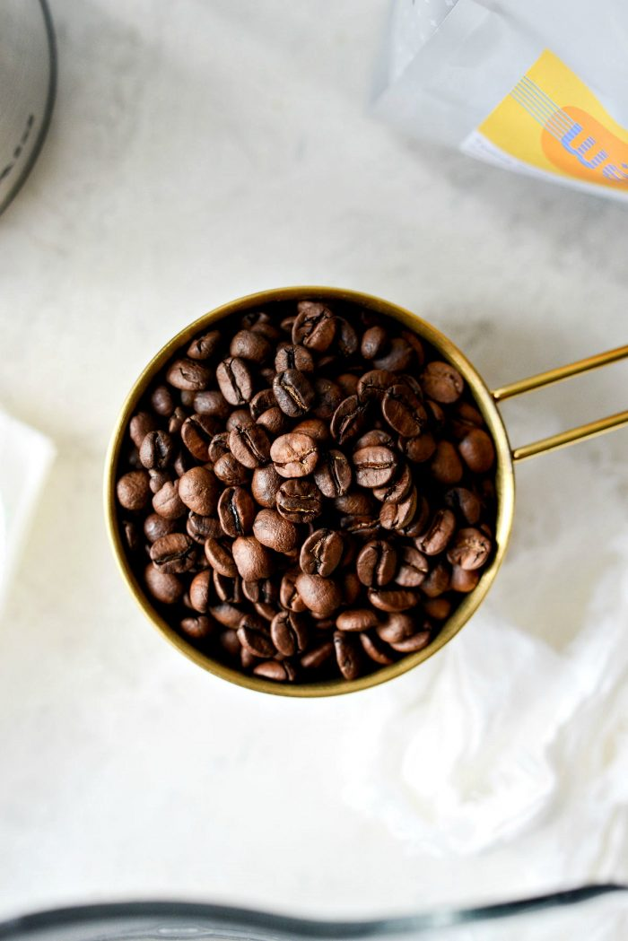 whole coffee beans in gold measuring cup