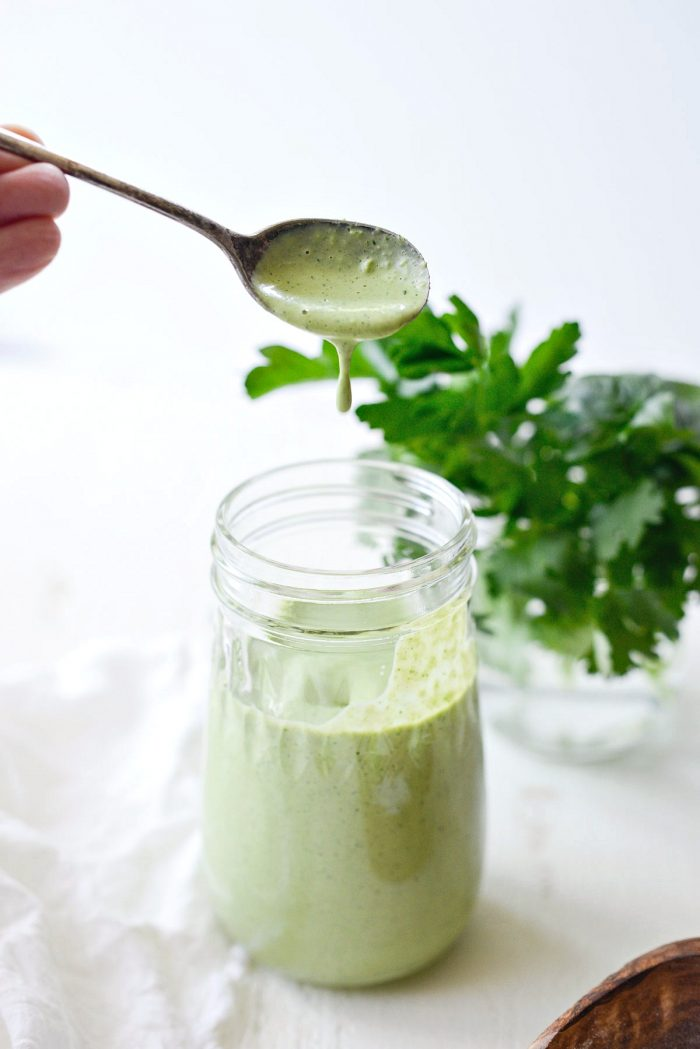 greek yogurt Green Goddess salad dressing dripping off a spoon