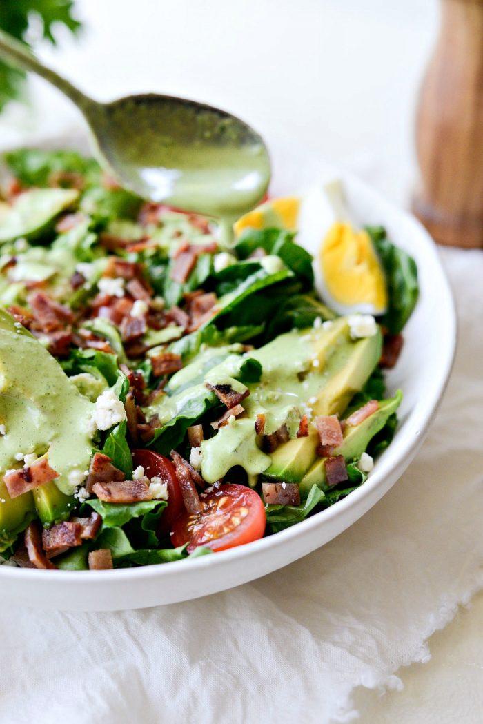 drizzling greek yogurt Green Goddess salad dressing on cobb salad.
