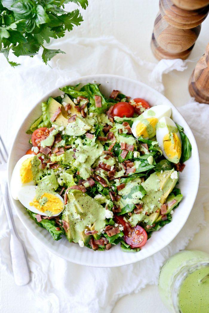 greek yogurt Green Goddess salad dressing on cobb salad in white bowl