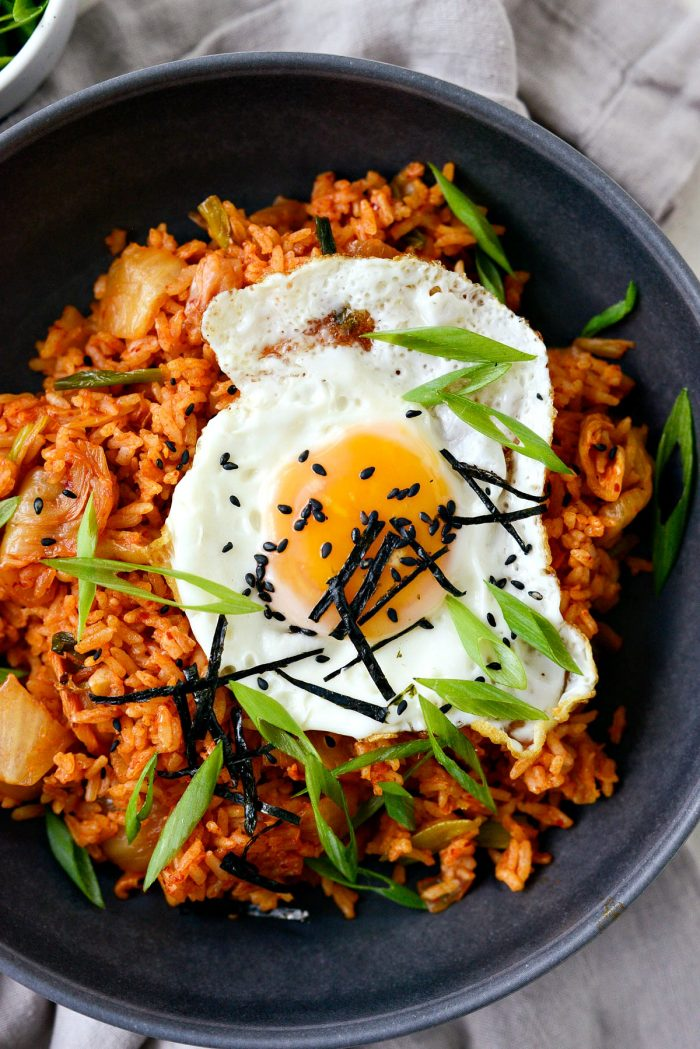 kimchi fried rice in black bowl with fried egg, black sesame seeds, green onion and nori