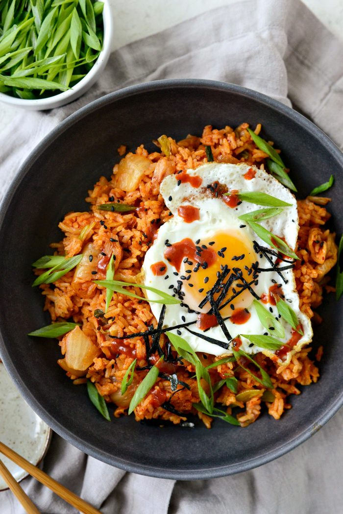 kimchi fried rice in black bowl with toppings and gochujang hot sauce.