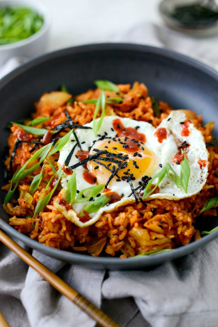 kimchi fried rice in black bowl with chopsticks