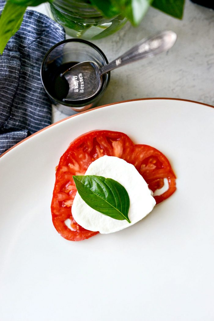 build the platter with a slice of tomato, mozzarella and basil