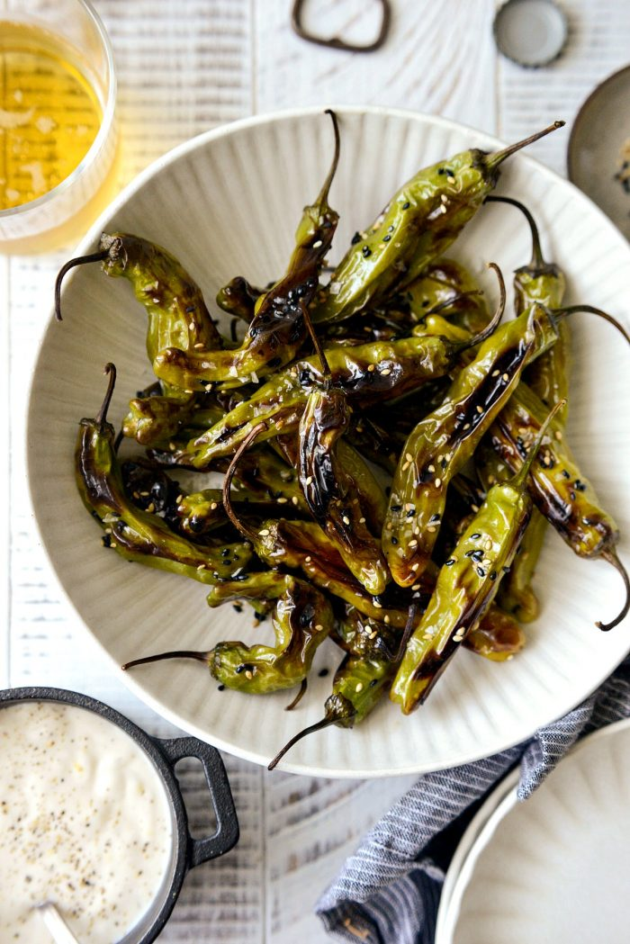 blistered shishito peppers in a cream bowl