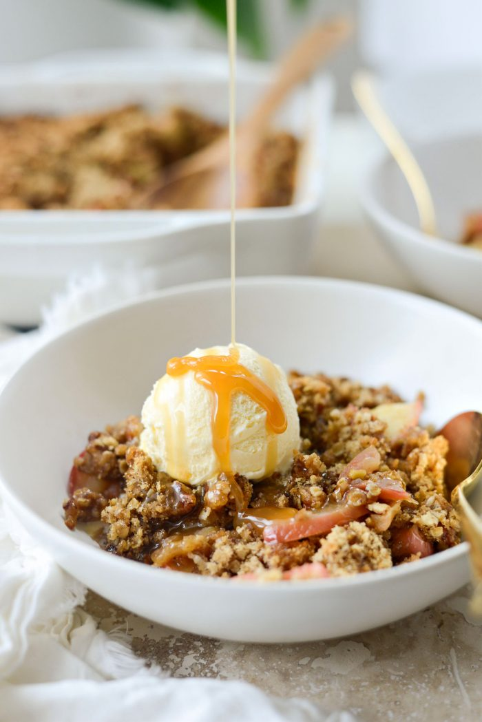 warm apple crisp with a scoop of ice cream and caramel drizzle.