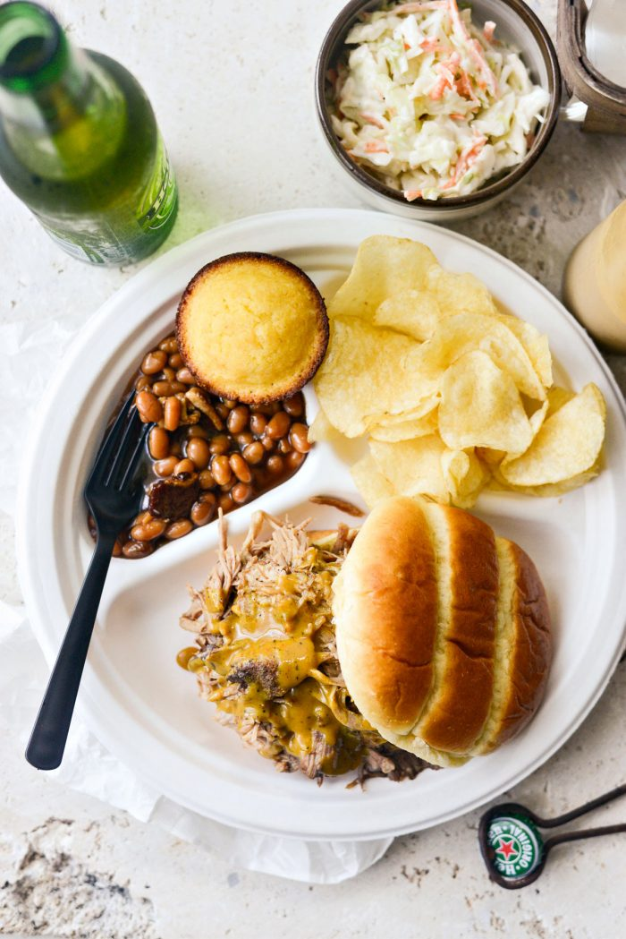 Plate of pulled smoked pork on brioche bun with beans, chips, cornbread and coleslaw.