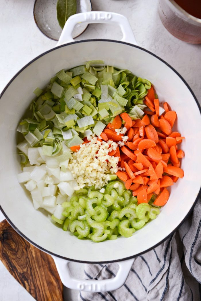 white dutch oven with onions, leeks, carrots, celery and garlic.