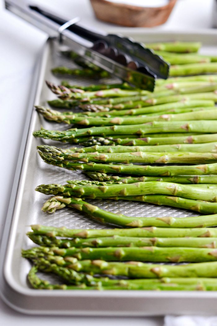 trimmed asparagus in shallow pan coated in olive oil.