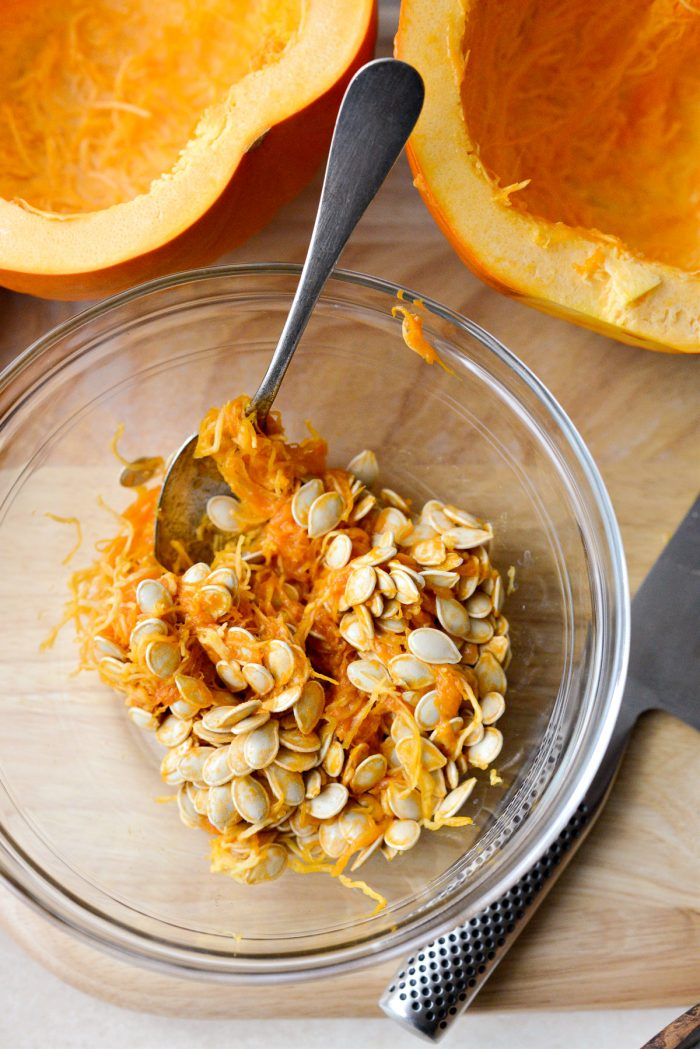 seeds and pumpkin guts in a glass bowl.