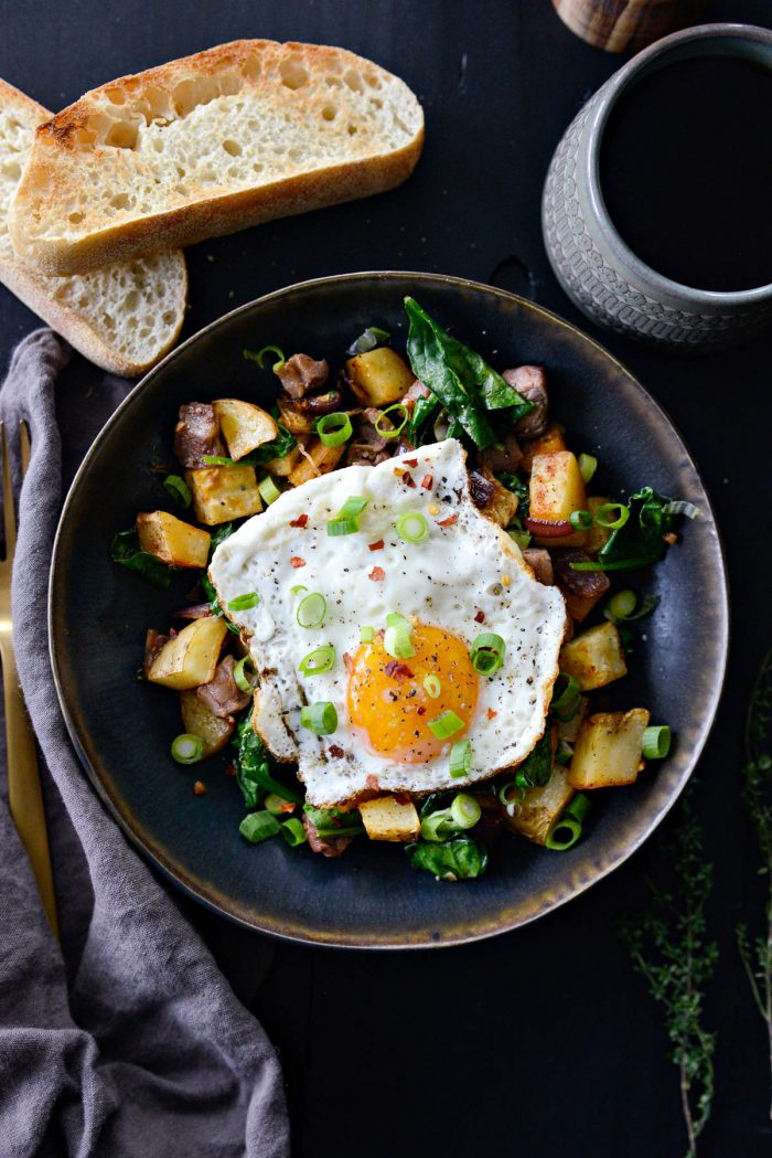 Leftover Prime Rib Breakfast Hash topped with fried egg and green onion.