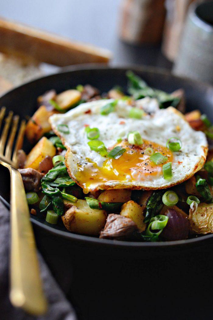 Leftover Prime Rib Breakfast Hash in black dish with gold fork.