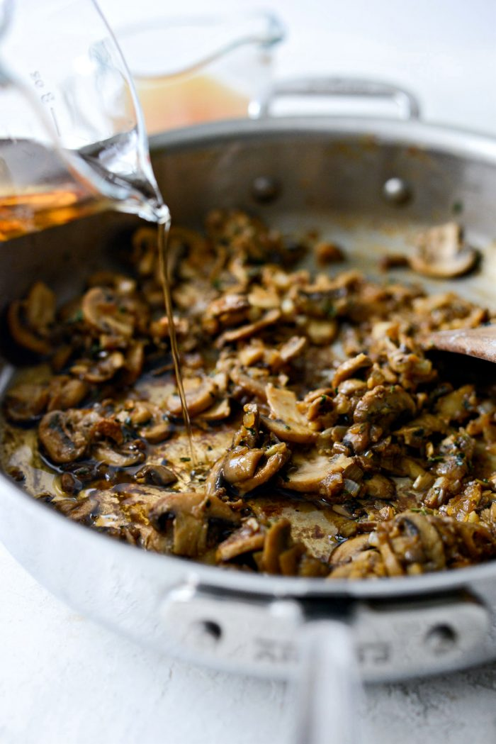 pouring marsala wine into skillet with mushrooms.