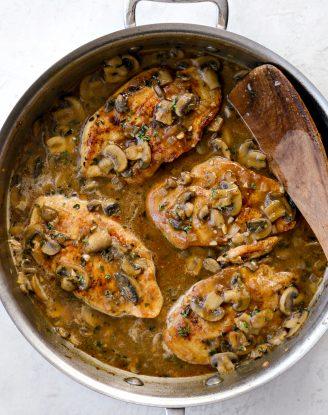Lighter Chicken Marsala in skillet with fresh herbs on top.