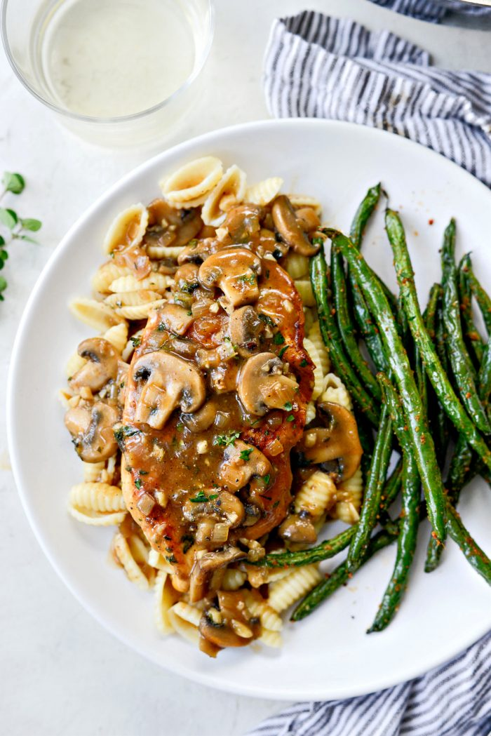 Lighter chicken marsala on white plate with green beans and pasta.